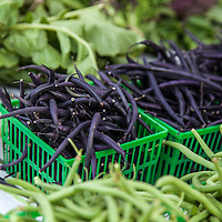 Baskets of green and purple beans at a farmers' market.