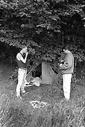 Men in front of a tent camouflaged by trees,  Glastonbury, Somerset, 1989