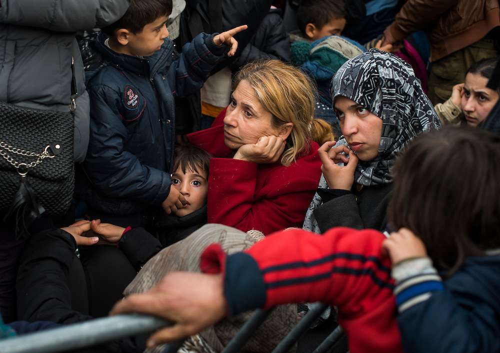 Refugees sit a few feet from the fence on the Macedonian border on March 6, 2016 in Idomeni, Greece. Hundreds waited, hoping to be part of the approximately 50 refugees who are let into Macedonia each day.