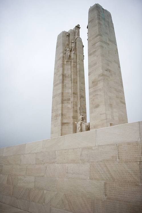 The front wall of the the Canadian National Vimy Memorial with the engraved names of the 11,285 Canadians killed in France.  In the back the twin white pylons of the Canadian National Vimy Memorial dedicated to the memory of Canadian Expeditionary Force members killed in World War one. The monument is situated at a 100 hectare preserved battlefield with wartime tunnels, trenches, craters and unexploded munitions. The memorial designed by Walter Seymour Allward opened in 1936.
