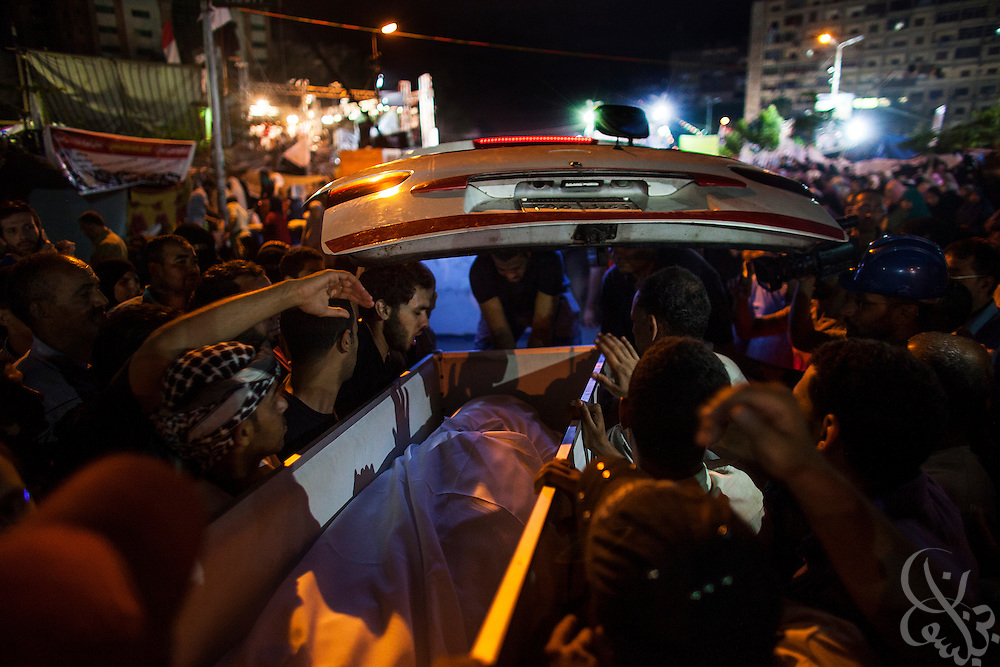 A coffin containing one of the 65 persons killed during early morning clashes July 27 is loaded into an awaiting ambulance at the entrance of the month-long sit-in by supporters of deposed President Mohamed Morsi at the Rabaah al-Adawia square in the Nasr City district of Cairo Friday July 28, 2013. In addition to the 65 killed, another 61 are on life support according to the Muslim Brotherhood and around 3000 injured by tear gas fired by authorities.