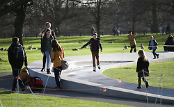 © Licensed to London News Pictures. 23/12/2015. London, UK. Visitors to Hyde Park enjoy the sunshine at the Diana, Princess of Wales Memorial Fountain. Photo credit: Peter Macdiarmid/LNP