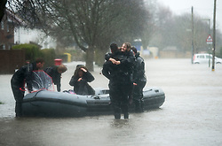 © London News Pictures. 12/02/2014. Egham, UK.  A young girl and her mother being rescued from their home in Egham, Surrey by members of the British Army Royal Engineers during heavy rainfall. Photo credit : Ben Cawthra/LNP