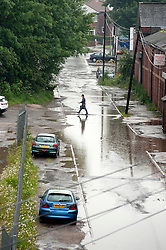 A man makes his way acroos the road between downpours using one of the few remaining pieces of High ground,  Butterthwaite Lane Sheffield..28 June 2012.Image © Paul David Drabble