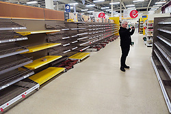 © Licensed to London News Pictures. 18/03/2020. Salford, UK. The Tesco branch , which normally opens until Midnight, closes two hours early as stock shortages become evident . A shopper photographs empty shelves at a branch of Tesco in Salford , which has sold out of all stock of all bread products as customers panic buy essentials , including toilet paper, pasta and hand sanitiser , in fear of a lockdown and shortages . Today the British Government announced further measures to combat the spread of Coronavirus ( COVID-19 ) , including school closures and further state support for those affected . Photo credit: Joel Goodman/LNP