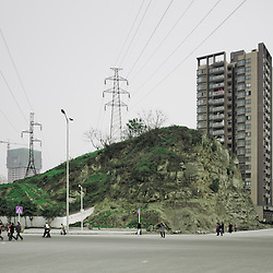 Chongqing - 30 gennaio 2011: un palo elettrico in una nuovissima area residenziale a nord di Chongqing. Nelle periferie della città, dove si costruisce mentre ancora non si è finito di demolire, si assiste ad accostamenti spesso incongrui. Talvolta buffi. Chongqing - January 30, 2011: An electricity pole on the border of a street crossing in a brand new area in northern Chongqing. In the suburbs, where they build when the demolishing is yet not finished, it is common to find constrasting elements, incongruous pairings. Funny sometimes.