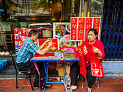 11 JANUARY 2019 - BANGKOK, THAILAND: A calligrapher writes Chinese New Year greetings on a table he set up in Bangkok's Chinatown while his wife dries greetings he wrote. Calligraphers set up tables throughout Chinatown in the weeks leading up to Chinese New Year. About 14% of Thais are of Chinese ancestory and Lunar New Year is widely celebrated in Thailand. Chinese New Year celebrations in Bangkok start on February 4, 2019. The coming year will be the Year of the Pig in the Chinese zodiac.       PHOTO BY JACK KURTZ