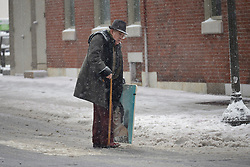 Philadelphia, PA, USA - February 20, 2019: Resident carrying a painting attempts to cross Market Street as Winter storm Petra brings several inches of snow to Philadelphia, PA, on February 20, 2019. The city is expected to receive five inches of snowfall before changing over to sleet.