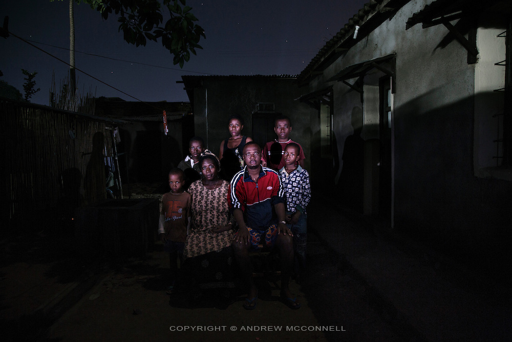 Congolese refugees, the Mwanmba family: (L-R) Didier, Leonardo, Bambi Byumbay Florence, 35, Marie Clementine, Didier Mwamba, Jean Kevin, and Eddy Joyeux, pictured at their home in Bujumbura, Burundi.<br /> <br /> Words of Bambi Byumbay Florence<br /> In 1996 there had been many rumours saying that people were coming from the outside to attack Congo. I remember it was raining, there were rumours that at the 7 in the evening we were told people would come form Mariba. Then a few minutes later we heard the attack and these people came. I remember we were in a house with 2 rooms and the toilets were outside. We had to go outside to hide, as it was very dark we saw people going inside the house, they searched but didn't find anything. They started a fire in my sisters room, when they did this my husband wanted to go out thinking that my sister was in that room because at that time she was only 10, he left the toilets to go inside the house, they got him then they asked him &quot;where were you?&quot; he said, &quot;I was only in the toilets&quot;, then they said &quot;we will close our eyes and then we don't want to see you again&quot;. So my husband left. <br /> <br /> When the house was on fire everything got burned, I stayed in the toilets, I spend the night there. Inside the house everything had been burned, even my diploma. We couldn't say who they were but I remember I was told that they were coming from Rwanda and Uganda, I remember we called them black people because they were really really dark. At around 10am young people came with the head of someone on a branch so we were obliged to flee, with this head we were really traumatised. Everywhere we passed there were dead bodies, when we crossed Uvira we headed to Mykibola Kigongo, everyone was heading there and everywhere there were dead bodies. Then we came to a checkpoint, here they would just look in your face and tell you to step aside, or for another person they could say &quot;ok continue&quot; and then for another one they could keep him and they could just decide on that ba