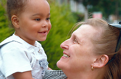Grandmother standing outside holding young girl smiling,
