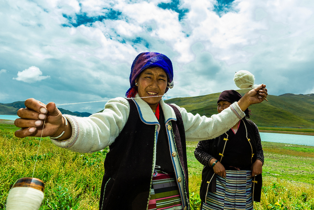 Tibetan woman spinning wool with 45 mile long Yamdrok Tso Lake (14,570 feet) in the background. It is the largest lake and one of the three sacred lakes in Tibet (Xizang), China.