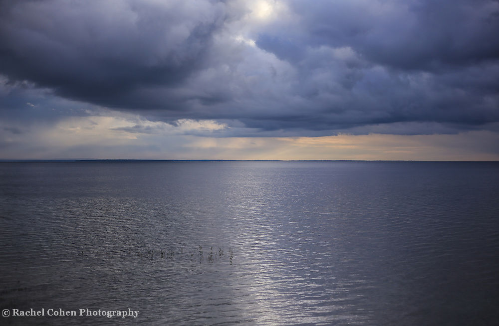 &quot;All that Shimmers&quot;<br /> <br /> Stormy skies just after sunrise on Lake Huron. Shimmering white sunlight reflects across the waters!<br /> <br /> Sunrise Images by Rachel Cohen