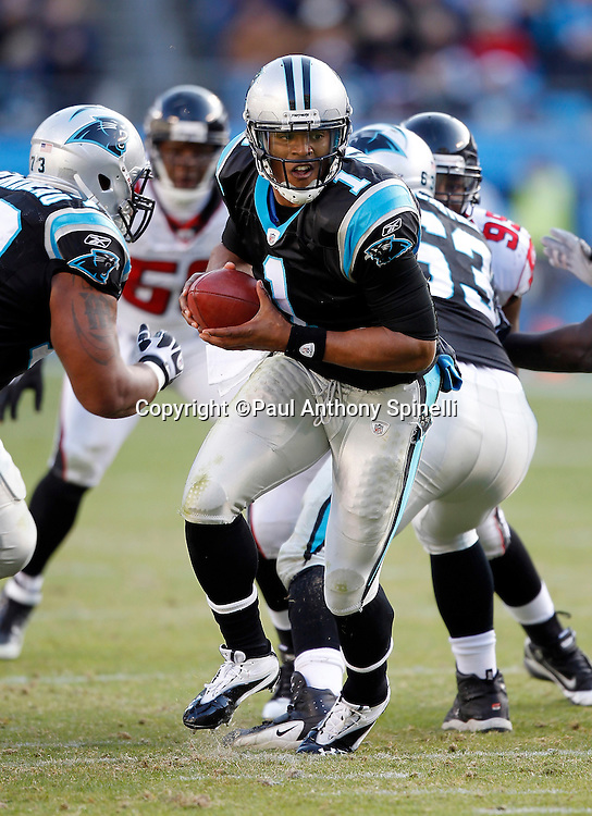 Carolina Panthers quarterback Cam Newton (1) looks to hand off the ball on a running play during the NFL week 14 football game against the Atlanta Falcons on Sunday, December 11, 2011 in Charlotte, North Carolina. The Falcons won the game 31-23. ©Paul Anthony Spinelli