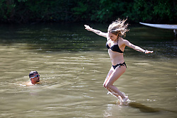 © Licensed to London News Pictures. 06/05/2018. London, UK. Ana Sofia jumps in Hampstead Heath Mixed Bathing Pond in north London as temperatures hit 27C on Sunday, May 6, 2018. Photo credit: Tolga Akmen/LNP