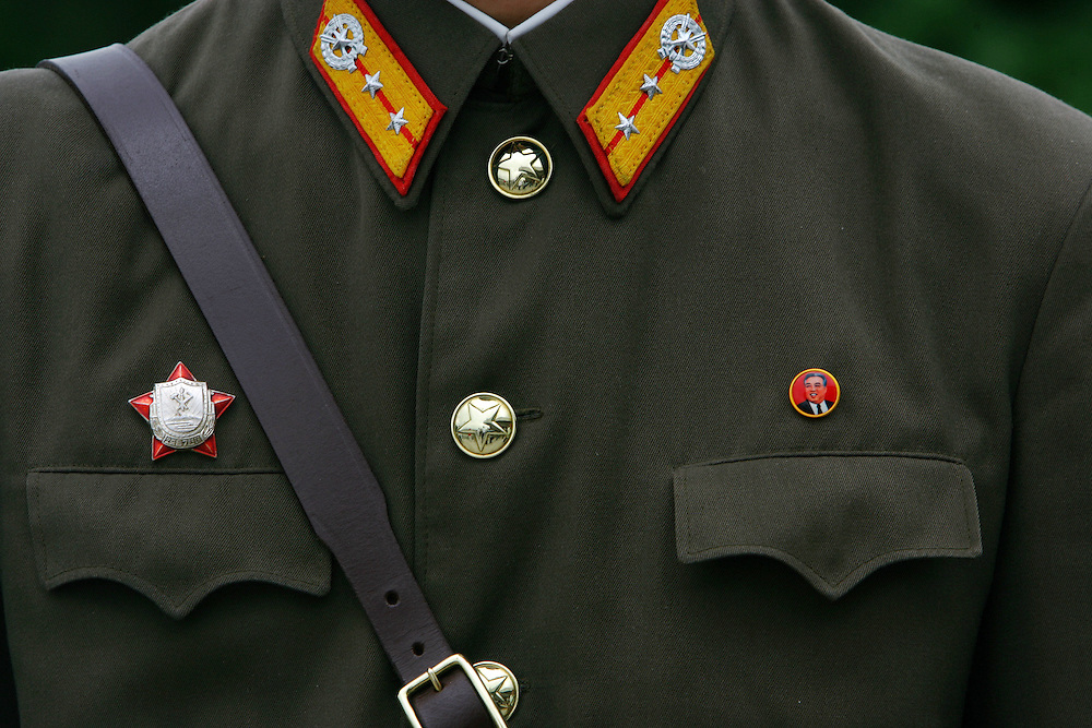 A North Korean soldier wears a pin showing the late President of North Korea Kim Il Sung on his uniform, as he stands outside of the house where the military armistice treaty was signed on the demarcation line in Panmunjon, on the border between North Korea and South Korea Tuesday Aug. 7, 2007.