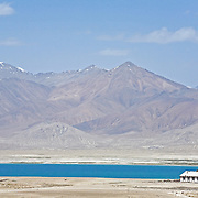 Lone house sits on banks of turquoise lake in desolate moonscape of Pamir plateau