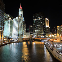 Chicago River skyline buildings at night with Dusable Bridge (Michigan Avenue Bridge), the Wrigley Building, 401 North Michigan Avenue (formerly The Equitable Building), and the Sun Times building.