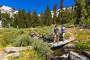 Hikers crossing footbridge in the Big Pine Lakes basin, John Muir Wilderness, California