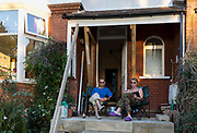 A couple sit with evening drinks on their Edwardian home's front porch during a re-build project, on 1st September 2018, in south London England.