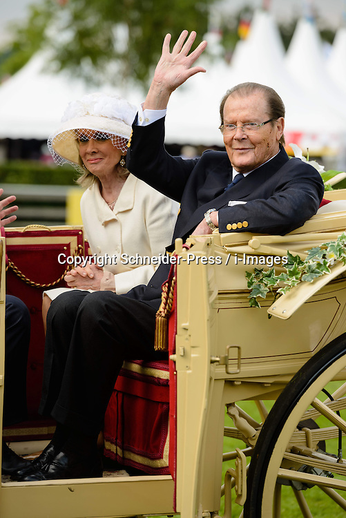 (L-R) Kristina Tholstrup, wife of Roger Moore and Actor Sir Roger Moore, UNICEF ambassador wave to the fans out of the carriage during the Opening Ceremony during day one of the 2013 CHIO Aachen tournament on June 25, 2013 in Aachen, Germany. Photo by Schneider-Press / i-Images. UK & USA ONLY