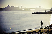 Girl walking her dog on a hot morning in the banks of the east river in DUMBO, Brooklyn, with the Williamsburg Bridge in the background, New York, 2008.