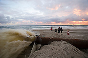 Sunset at the beach. Pumping up sand from off-shore to stabilize the beach, threatened by erosion caused by the North Sea waves.