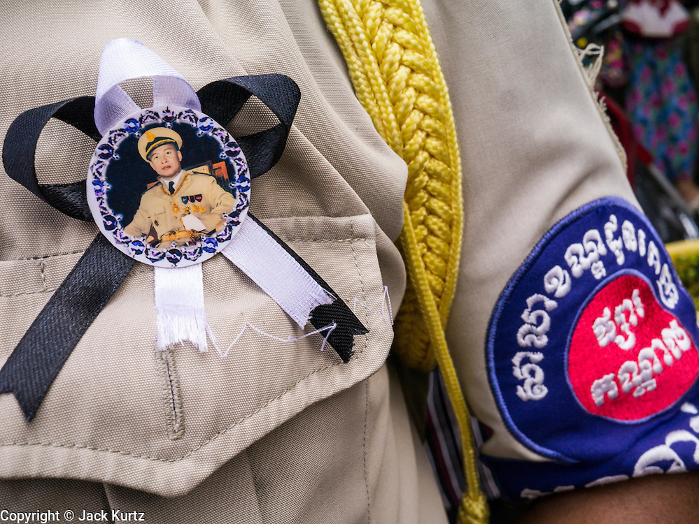 31 JANUARY 2013 - PHNOM PENH, CAMBODIA:    A Cambodian policeman wears a black ribbon with a portrait of King Norodom Sihanouk during the mourning period for Sihanouk, who ruled Cambodia from independence in 1953 until he was overthrown by a military coup in 1970. Sihanouk died in Beijing, China, in October 2012.     PHOTO BY JACK KURTZ