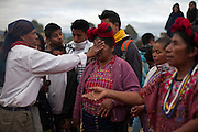 An Ajq'ij, or Mayan Spiritual Guide, places his hand over a woman's face in an act of blessing during celebrations in the ancient Mayan site of Zaculeu marking the end of the Mayan Era known as 13 Baktun. Zaculeu, Huehuetenango, Guatemala. December 21, 2012.