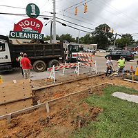 Workers with Tupelo Public Works wait for cement truck to arrive as they work on relacing curbs and sidewalks along South Madison Street at Main Street.