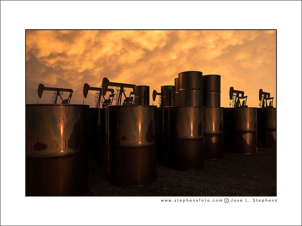Oil pump machines and barrels at sunset