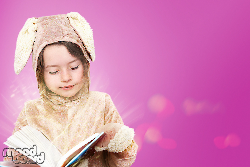 Little girl dressed as a bunny rabbit reading a book