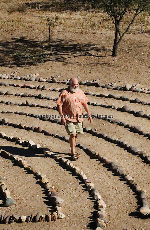 Dr. Andrew Weil at his 120 acre ranch that borders on the Saguaro National Park about 15 miles south of Tucson, Arizona. On his ranch property, Dr. Weil walks the stone labyrinth that has only one path to the center from the outside.