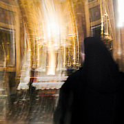 Blurred motion images of woman with black veil and coat at Chiesa Santa Maria della Vittoria, Rome, Italy