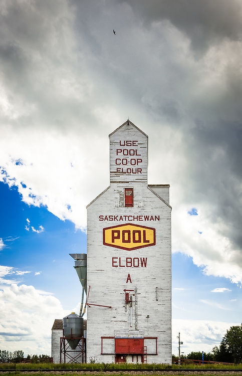 """Constructed in 1913 and upgraded in 1957 and 1974, this is an excellent example of a traditional wooden cribbed-construction, gable-roofed elevator with gable-roofed cupola. The """"standard plan"""" elevator, circa 1910 - 1965, typically stood 50 to 60 feet high, with approximately 40,000 bushel capacity. The Saskatchewan Wheat Pool donated the elevator to the Village of Elbow in 2007 to use as a museum."""