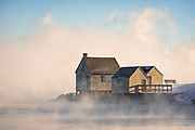 The iconic fishing shacks on Fisherman's Point, Willard Beach, look stunning in early morning light with a heavy mist pouring off of the relatively warmer water on this frigid day.