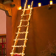A kiva ladder adorned with Christmas lights and traditional luminarias lighting the ruins are part of the holiday festivities at the Coronado Sate Monument historic site in Bernalillo, New Mexico.