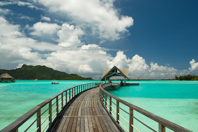 A boardwalk winds towards a boat dock over water in the turquoise lagoon waters in Bora Bora, Tahiti