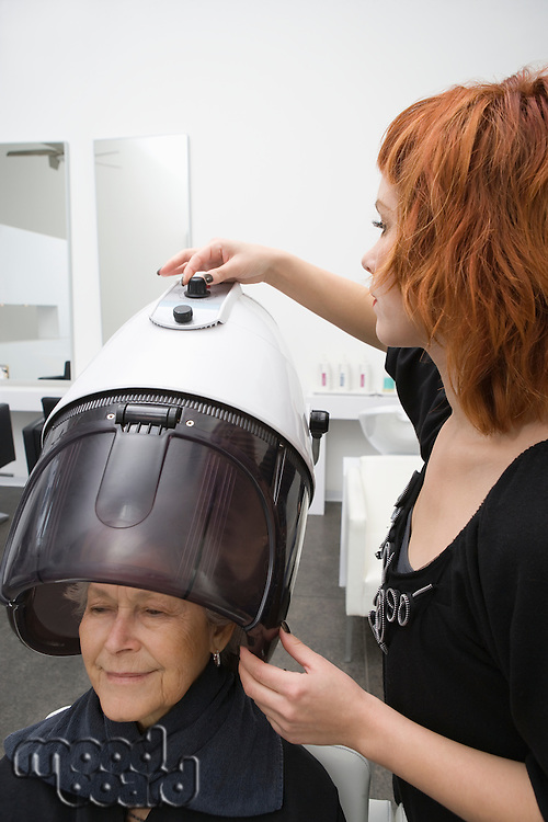 Eldelrly woman sits under hairdrying hood