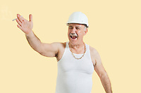 Senior male constructor shouting over yellow background