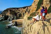 Family watching the surf from a cliff along US Highway 1 on the Pacific coast, Big Sur, California