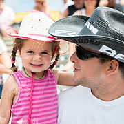 A little girl attend the local rodeo on the knees of her father.