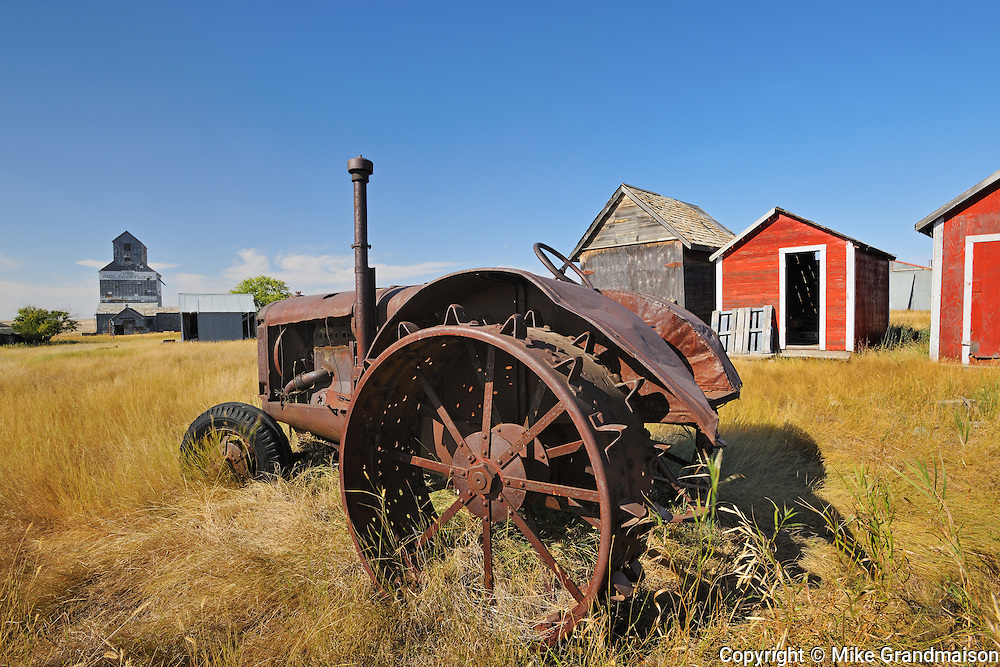 Old tractor, sheds and grain elevator in ghost town<br /> Fusiller<br /> Saskatchewan<br /> Canada