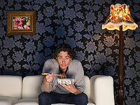 Young man sitting on sofa holding take out food