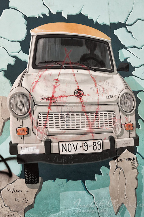A Trabi goes through the wall in the East Side Gallery. This painting is a work of Birgit Kinder.