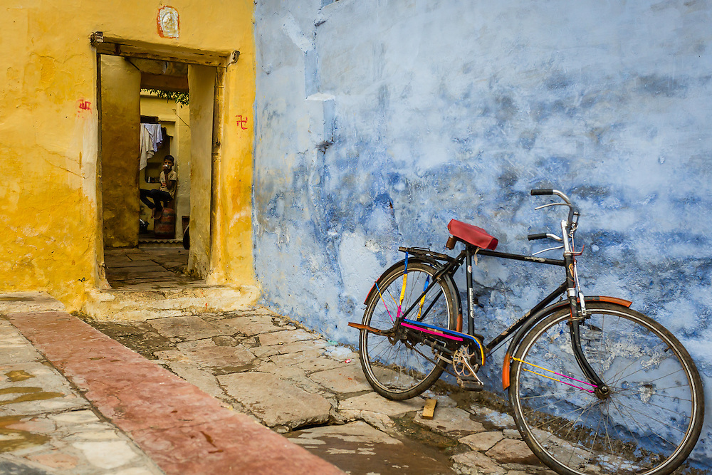 A bycicle stands near a ble wall as a boy watches from inside his house while having breakfast.