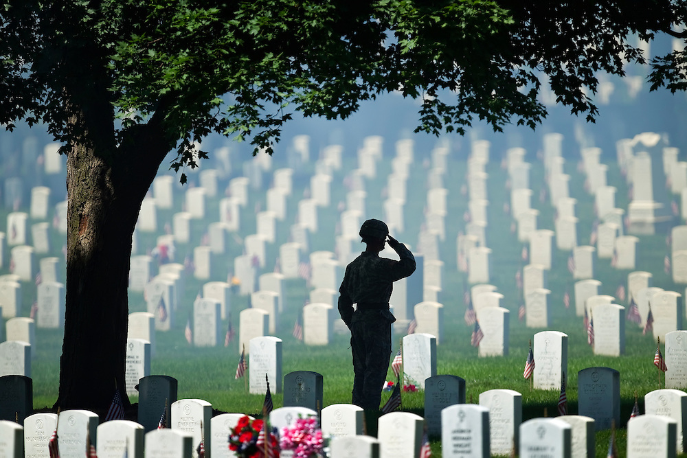 """With artillery smoke hanging in the air from a 21-gun salute by his company at Fort Leavenworth, the 500th Military Police Detachment, Army Sgt. Travis Smith saluted during the playing of """"Taps,"""" during Monday's Memorial Day ceremony at Fort Leavenworth National Cemetery."""