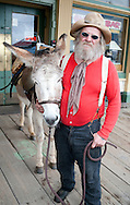 """Stinky"" and his donkey Bernadine roam the streets of Virginia City, Nev., on Saturday, April 23, 2011. He is among docents who tell tales of the 19th century mining city, and gladly accepts donations to keep Bernadine in carrots. The rescue donkey is named after his wife, he said. The Comstock Lode turned Virginia City and surrounding mining communities into boomtowns as people sought their fortunes in gold and silver. (© 2011 Cindi Christie/Cyanpixel® Photography)"