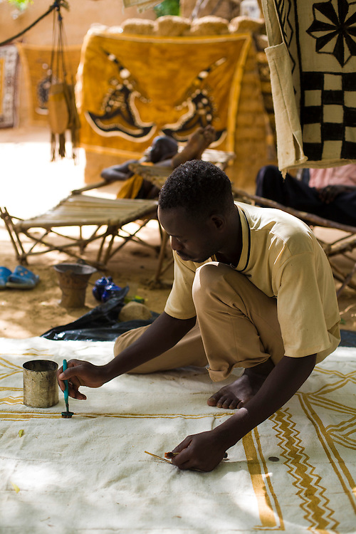 Artisan painting a cotton clothe with a dye made with mud and tree-bark. So-called bogolans are one of the most traditional malian souvenir and each ethnic group has its own tipical design.