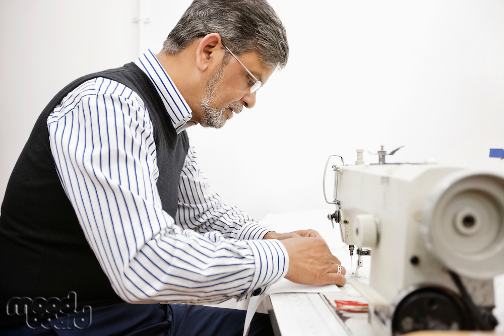 Profile of middle aged tailor using sewing machine
