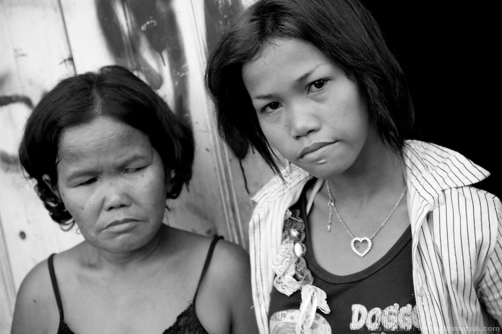 "Mother and daughter (Jene, who says she is 19) at home in a slum where the non governmental organization ""Acting for Women in Distressing Situations"" (AFESIP), conducts outreach and provides services in Phnom Penh, Cambodia. The permanent structure, a decaying four story building known simply as 'The Building', was built in the 1960's as transitional housing and now hosts a shantytown where many of the city's poor live, including many prostitutes, and is believed to have the highest rate of HIV infection in the city. AFESIP hands out free condoms, instructs prostitutes on HIV prevention, and conducts outreach in case the prostitutes need medical services, choose to leave their profession, or can report on cases of sex trafficking. AFESIP offers housing, education, training, and counseling for women who are victims of sex trafficking, worked as prostitutes, or are escaping domestic violence. Founded by Somaly Mam, who herself was once a prostitute and victim of trafficking and domestic abuse, AFESIP has three facilities in Cambodia and works with other NGO's to provide long term care for the women."